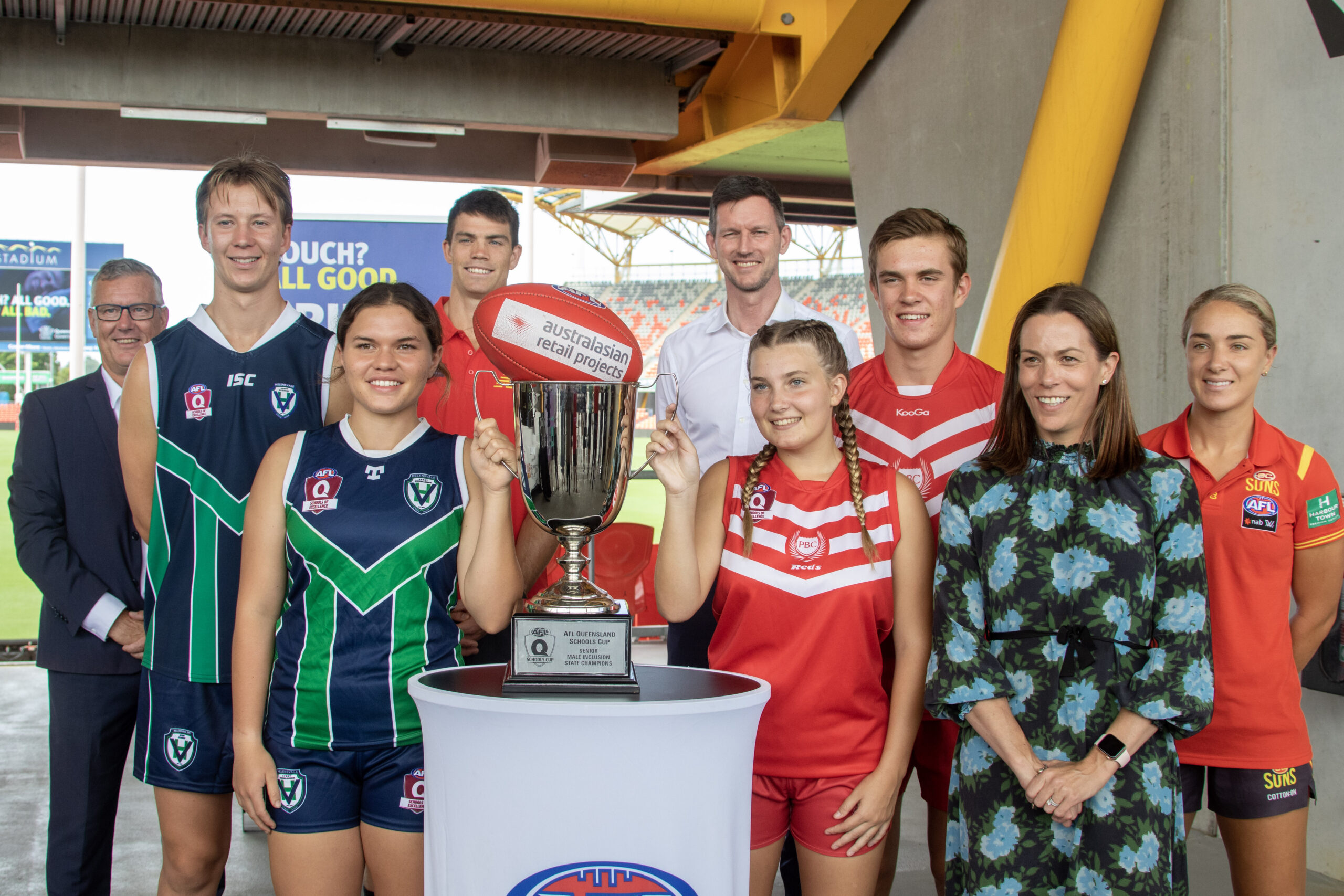 Head of AFL Q Trish Squires, Transport Minister Mark Bailey and Gold Coast SUNS CEO Mark Evans with students from Palm Beach Currumbin and Helensvale HS